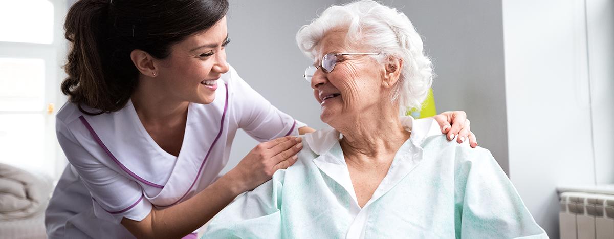 Pflegehilfskraft mit Bewohnerin im Pflegeheim